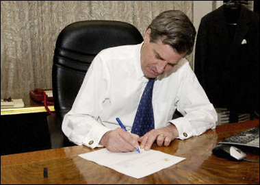 Paul Bremer signs Iraqi sovereignty document in his office at the Coalition Provisional Authority headquarters